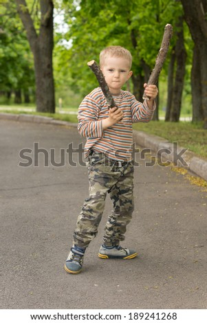 Determined macho little boy stick fighting brandishing two blunt sticks in his hands as he poses in the middle of a rural road - stock photo