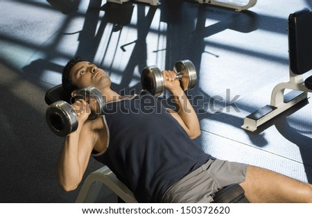 Determined man exercising with dumbbells in health club - stock photo