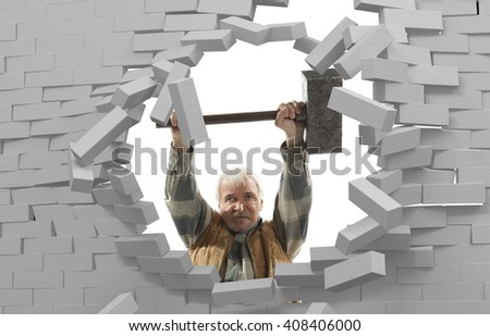 Determined man with hammer in hands and brick wall - stock photo