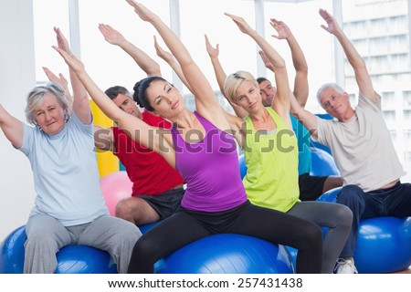 Determined men and women on fitness balls exercising in gym class - stock photo