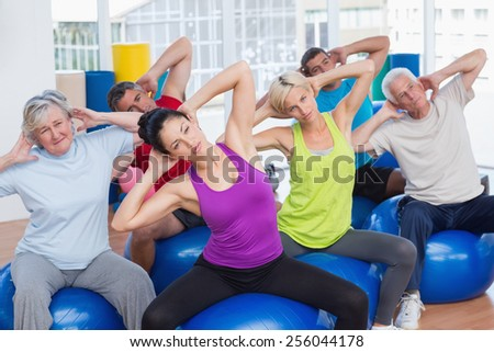 Determined people on fitness balls exercising in gym class - stock photo