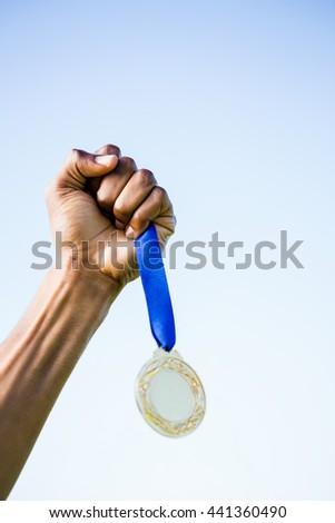 Determined relay athlete running with baton running track - stock photo