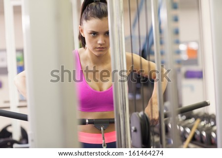 Determined sporty young woman doing exercises in the gym on lat machine - stock photo