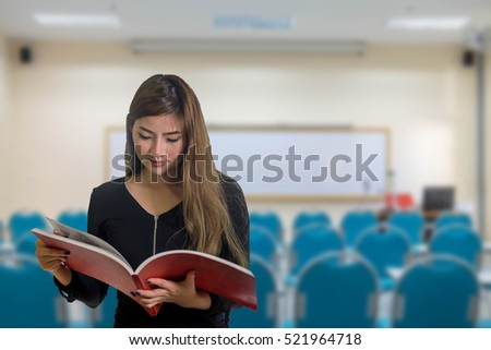 Determined student with text books doing homework in school classroom