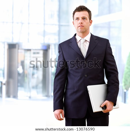 Determined successful businessman standing and holding laptop computer in hand, outdoor in front of office building. - stock photo