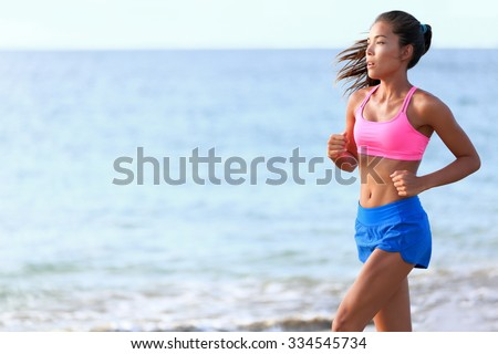 Determined woman jogging on beach. Fit young female is in sports clothing. Jogger is exercising against ocean during sunny day. - stock photo