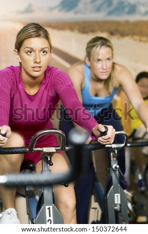 Determined women exercising on bikes in health club - stock photo