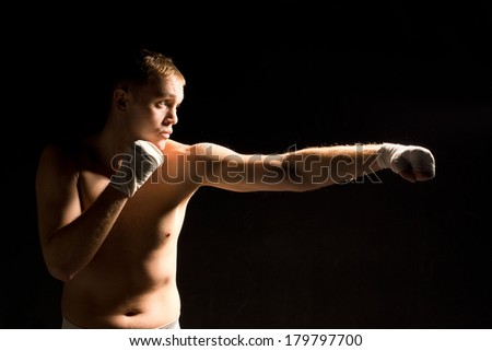 Determined young boxer throwing a punch during training or a match extending his left arm in a jab against a dark background with copyspace - stock photo