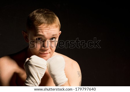Determined young boxer with his bandaged fists held at the ready in front of his chest facing off against the camera on a dark background with copyspace - stock photo