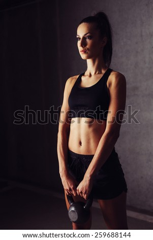 Determined young female athlete holding kettlebell in both hands - stock photo