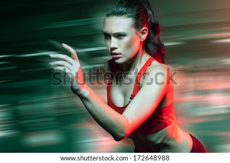 Determined young female sprinter running at speed showing a motion blurred background as she competes in a race or does a workout on the track during training - stock photo