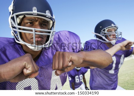Determined young football players looking away while playing on field - stock photo