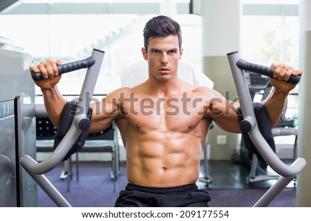 Determined young muscular man working on fitness machine at the gym - stock photo