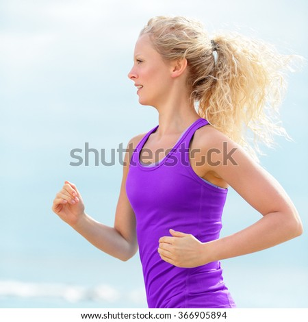 Determined young woman runner  jogging at beach. Fit blond female running is wearing purple tank top. Jogger is exercising during summer. - stock photo