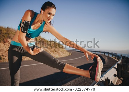 Determined young woman warming up before a run. Female athlete stretching her leg on road guardrail in morning. - stock photo