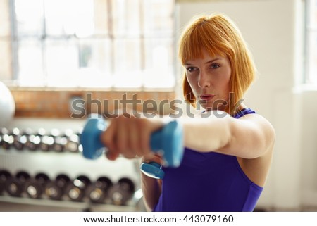 Determined young woman working out with dumbbells as she extends her hand with a weight towards the camera, focus to her face - stock photo