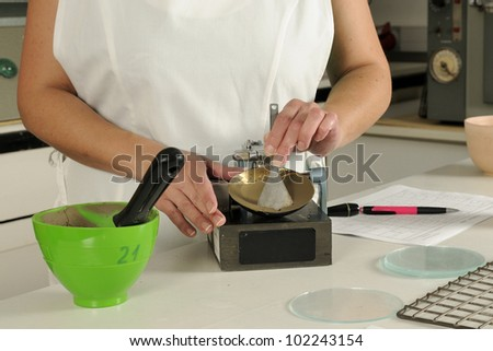Determining the liquid limit of soil using Casagrande apparatus in the soil laboratory. Cup with soil sample and grooving tool. - stock photo