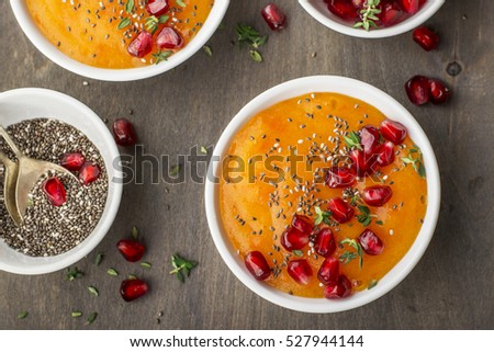 Detox and healthy breakfast smoothie of ripe juicy fruits of persimmon, pomegranate seeds, chia seeds with honey and thyme on a dark wooden background. Top view. The concept of organic food.