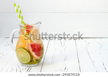 Detox citrus infused flavored water. Refreshing summer homemade cocktail with lemon, lime, orange and grapefruit. Copy space background. - stock photo