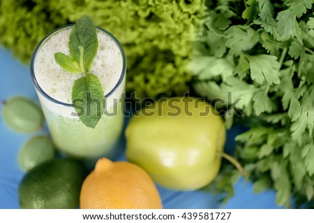 Detox  diet,  healthy food concept. green smoothie in glass and colored vegetables on natural blue wooden background