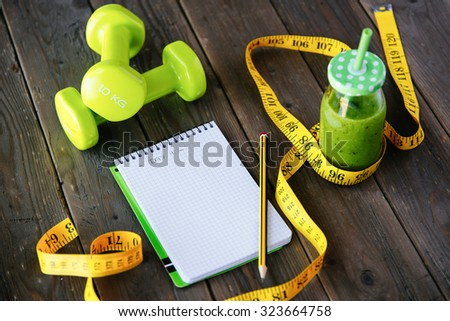 Detox green smoothie, blank copyspace notebook and measuring tape on wooden table for dieting and healthy fitness nutrition concept. Workout routine and diet planning. - stock photo