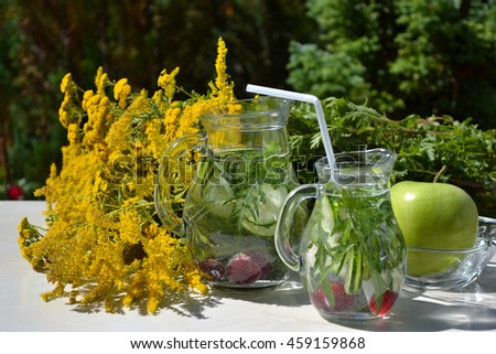 Detox infused vegetable flavored water in glass jugs.  Homemade summer refreshing drink with fresh cucumber slices,arugula, parsley and cherry. - stock photo