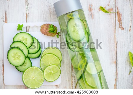 Detox Infused Water with Cucumber, Lime and Mint in Sports Bottle, with cut pieces of cucumber and lime nearby - stock photo