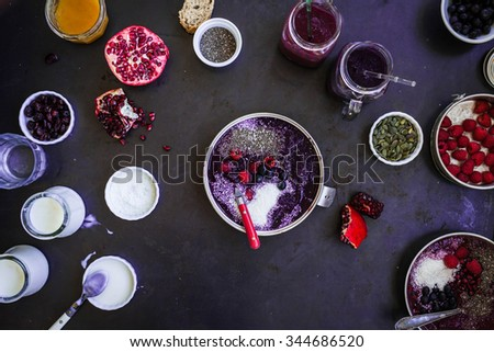 Detox smoothie bowl concept. High angle view of prepared colorful breakfast chia coconut smoothies over dark  table with various tropical fruits and jars of yogurt. Healthy breakfast bowl concept. - stock photo