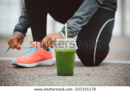 Detox smoothie drink and running footwear close up. City outdoor workout and fitness healthy nutrition concept.  Female athlete tying sport shoes laces before training. - stock photo