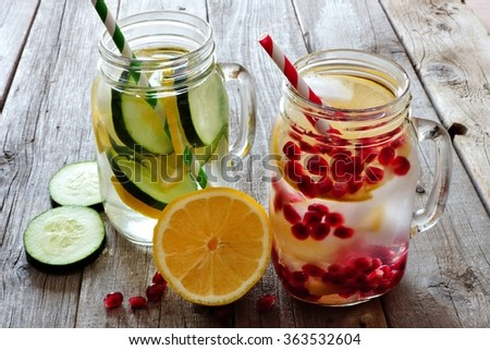 Detox water in mason jar glasses with lemon, cucumber and pomegranate against a rustic wood background - stock photo