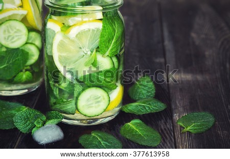 Detox water with lemon, cucumber and mint on rustic wooden background - stock photo