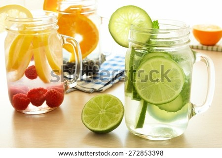 Detox water with various types of fruit in mason jars on a table - stock photo