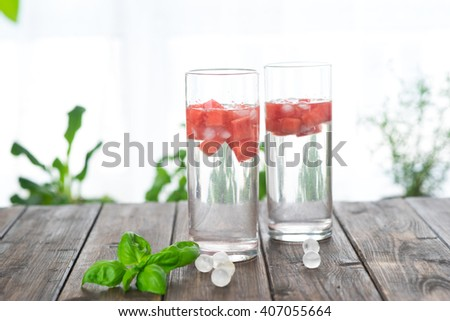 Detox water with watermelon and ice in two glasses on wooden table next to window - stock photo