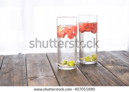 Detox water with watermelon and kiwi in two glasses on wooden table placed next to window - stock photo