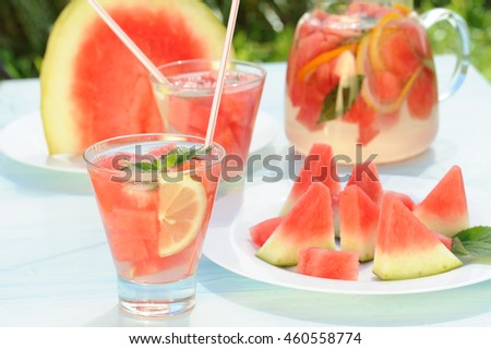 Detox water with watermelon and lemon on rustic table in the garden