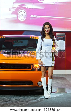 DETROIT - JANUARY 13 : A model poses with the Dodge Challenger at the North American International Auto Show media preview  January 13, 2014 in Detroit, Michigan. - stock photo