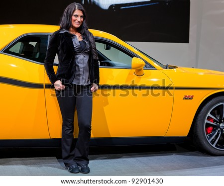DETROIT - JANUARY 11: A model strikes a pose with the Dodge SRT Challenger at the 2012 North American International Auto Show Industry Preview on January 11, 2012 in Detroit, Michigan.