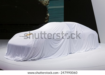 DETROIT - JANUARY 12: A Porsche sits covered ready to be unveiled January 12th, 2015 at the 2015 North American International Auto Show in Detroit, Michigan. - stock photo