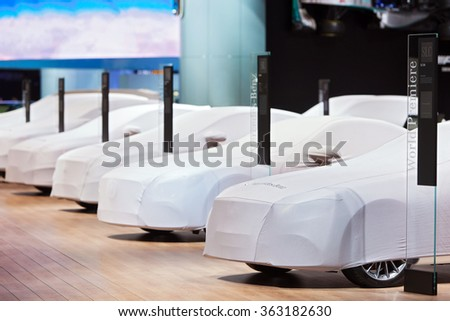 DETROIT - JANUARY 13: A row of covered Mercedes Benz at the North American International Auto Show media preview January 13, 2016 in Detroit, Michigan. - stock photo