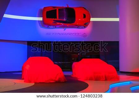 DETROIT - JULY 14 : Vintage Corvettes sit under covers at the 2014 Chevrolet Corvette unveiling January 14, 2013 in Detroit, Michigan. - stock photo