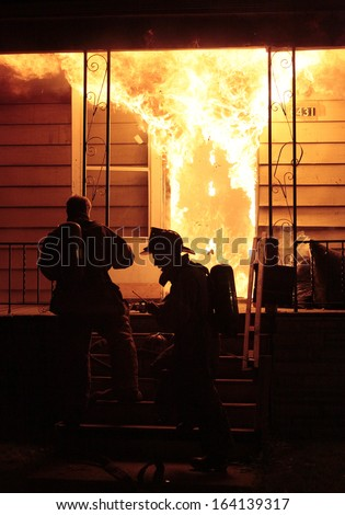DETROIT, MI - AUGUST 18 2012: Firefighters battle a blaze in a vacant home on Perkins Street on the southwest side of Detroit.