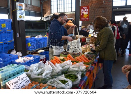 DETROIT, MI - FEBRUARY 6:  A vendor bags produce for a customer at Eastern Market, the largest historic public market district in the United States, on February 6, 2016.