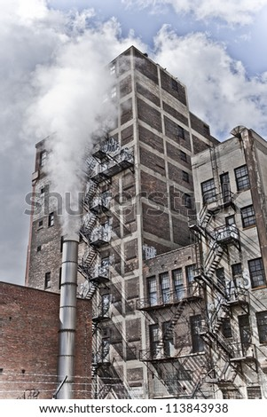 Detroit Michigan city view. There is an old building with graffiti and a fire escape along it's side. There is a steam pipe in front creating an eerie feel. - stock photo