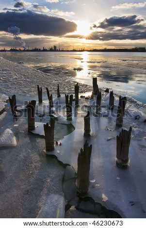 """Detroit River still packed with ice blocks, seen from Windsor, ON. In the background the industrial suburbs of Western Detroit are """"frozen"""" by a spectacular sunset. - stock photo"""