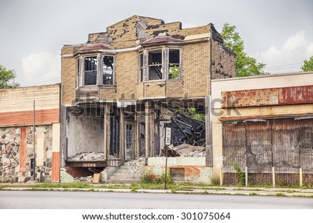 DETROIT, USA - JUNE 9, 2015: A burned out and semi-demolished building between two closed storefronts on Hamilton Avenue in Detroit symbolizes the urban blight that is emblematic of the city today.