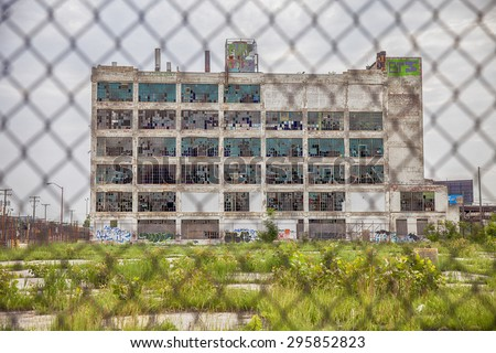 DETROIT, USA - JUNE 12, 2015: The Fisher Body Works factory in Detroit produced autos from 1919 to 1984. After the plant closed, weeds filled the parking lot and the walls were covered in graffiti.