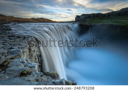 Dettifoss. Situated in Vatnajokull N.P. in Northeast Iceland, it's the most powerful waterfall in Europe. Photo taken from the east bank at sunset. - stock photo