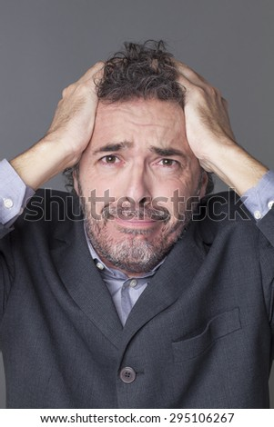 devastated businessman holding his head with both hands crying and expressing dramatic mistake at work