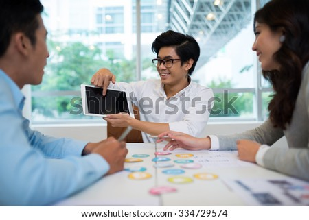 Developer showing new application to his colleagues at the meeting