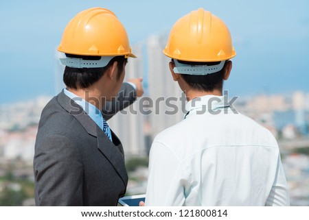 Developers looking over an urban panorama choosing an appropriate construction site - stock photo